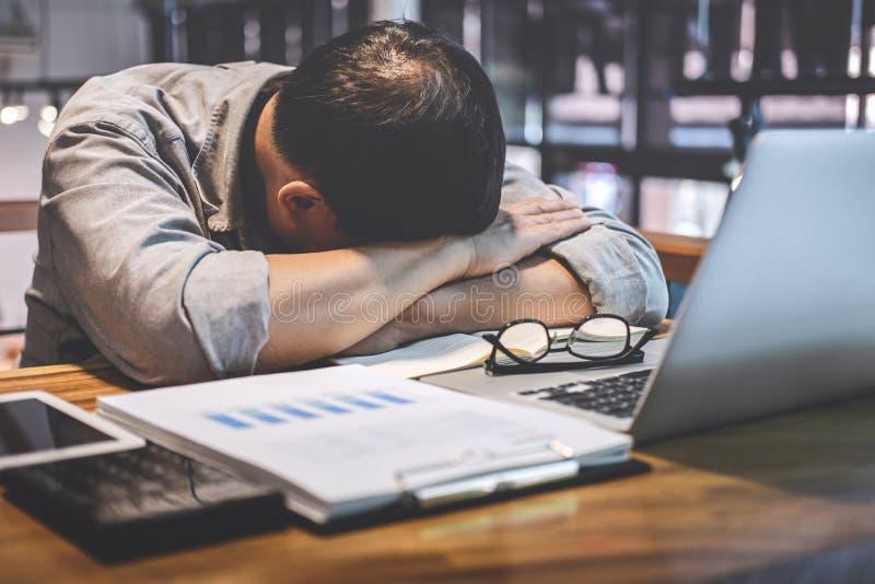 De slaapzakenman, Vermoeide hogere zakenmanslaap die lange werkdag hebben werkte zich op lijst in zijn bureau over royalty-vrije stock afbeeldingen