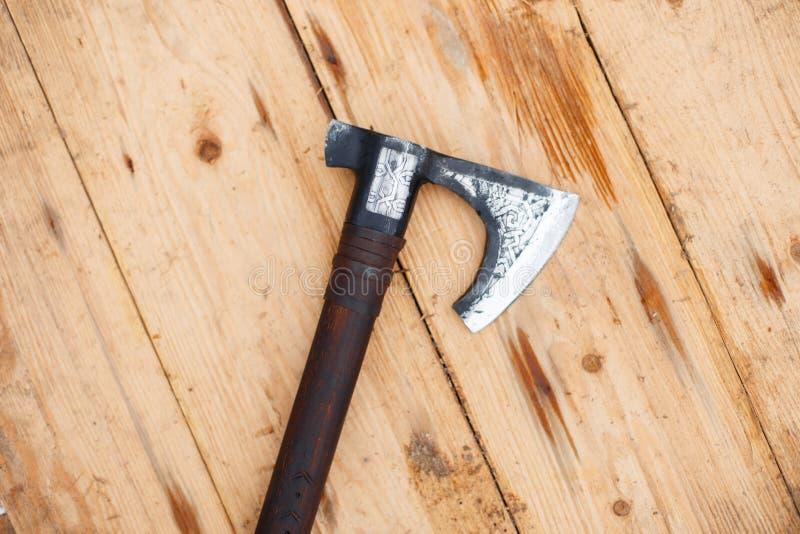 De slagbijl van de Vikingen ligt op een houten schild stock foto's