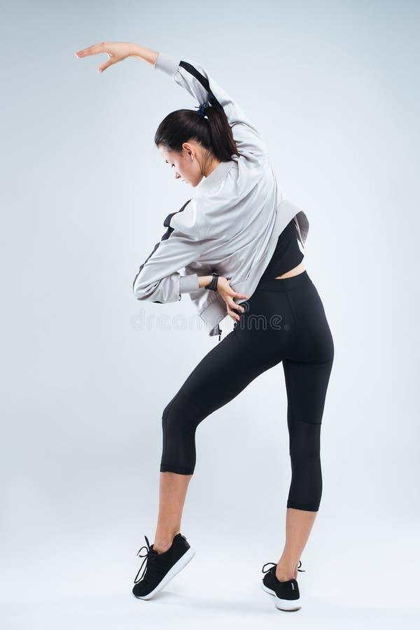 De slanke en sport jonge vrouw die en sport stellen doen oefent status met haar terug naar de camera en het uitrekken zich wapens royalty-vrije stock foto's