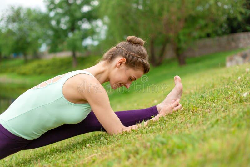 De slanke jonge donkerbruine yogi voert complexe yogaoefening op groen gras in de zomer op een achtergrond van aard uit royalty-vrije stock foto's