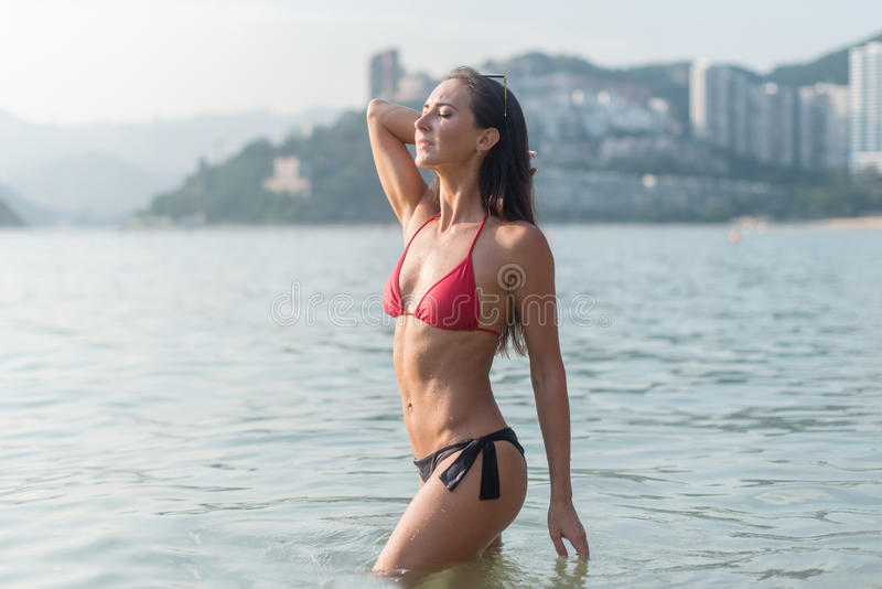 De slanke jonge vrouw die bikini dragen die zich in overzees met haar ogen bevinden sloot het nemen van diepe adem genietend van  royalty-vrije stock afbeelding