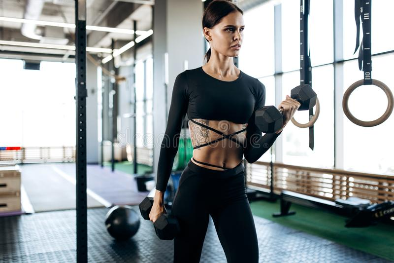 De slanke jonge vrouw met tatoegering gekleed in een zwarte sportkleding doet oefeningen met domoren in de gymnastiek stock foto's