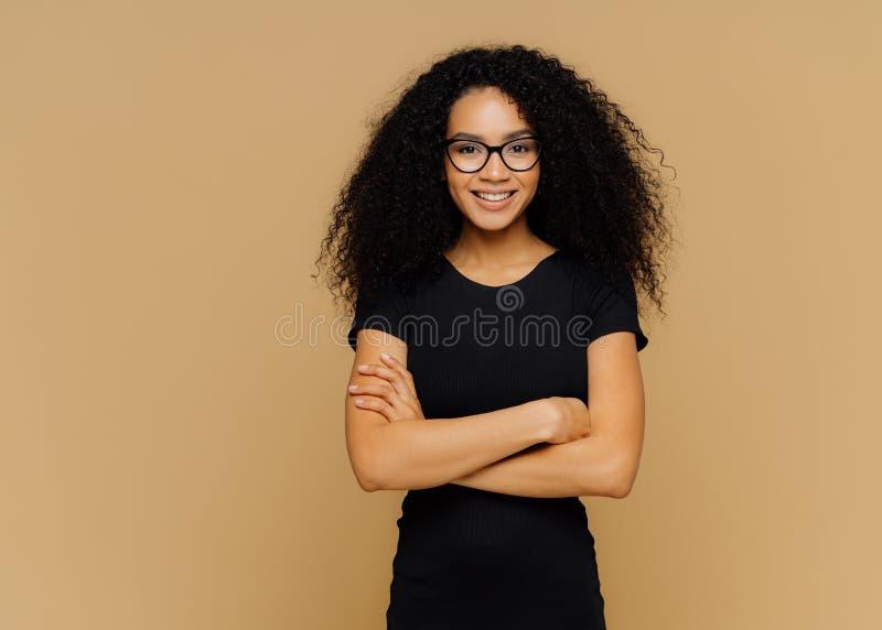 De slanke tevreden vrouw met Afro-kapsel, draagt zwarte vrijetijdskleding, optische glazen, heeft zekere uitdrukking, luistert royalty-vrije stock afbeelding