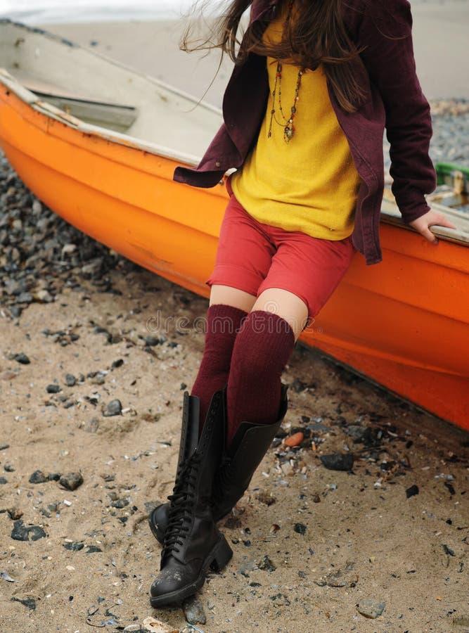 De slanke vrouwenbenen gressed in gebreide kousen, zittend op een boot op een strand royalty-vrije stock afbeelding