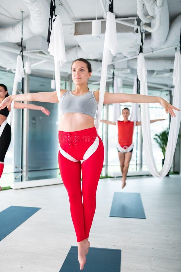 De slanke yogatrainer in het rode beenkappen tonen stelt voor antigravity yoga stock foto