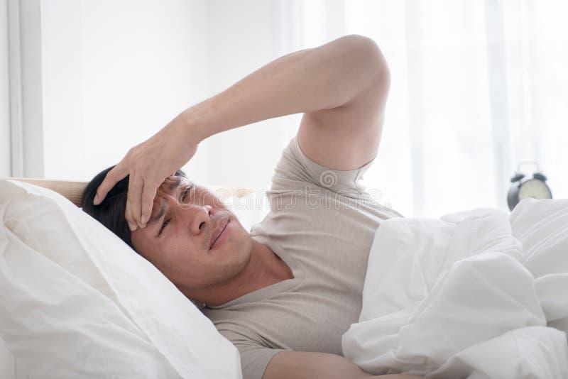 De slapeloze mens op bed ontwaakte met hoofdpijn stock afbeeldingen