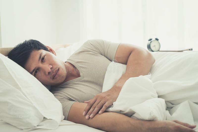 De slapeloze mens op bed ontwaakte met hoofdpijn royalty-vrije stock afbeelding