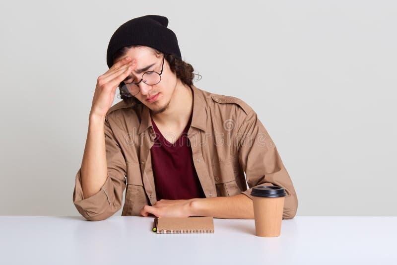De slaperige kerel met vermoeid en axhausted gelaatsuitdrukking, zittend bij bureau dichtbij notitieboekje en de kop van koffie,  royalty-vrije stock afbeeldingen