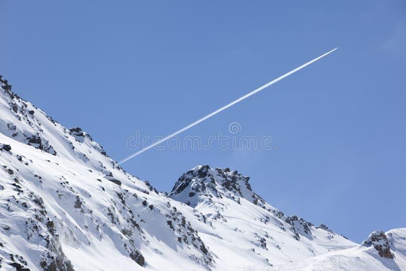 De sleep van het vliegtuig over sneeuwberg stock fotografie