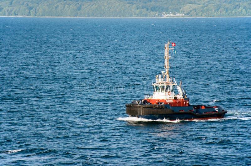 De sleepboot AROS navigeert op het overzees om een cruiseschip bij te staan die de haven ingaan royalty-vrije stock afbeeldingen