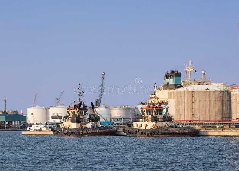 De sleepboten legden bij een olieraffinaderij vast op zonnig, Haven van Antwerpen, België royalty-vrije stock foto