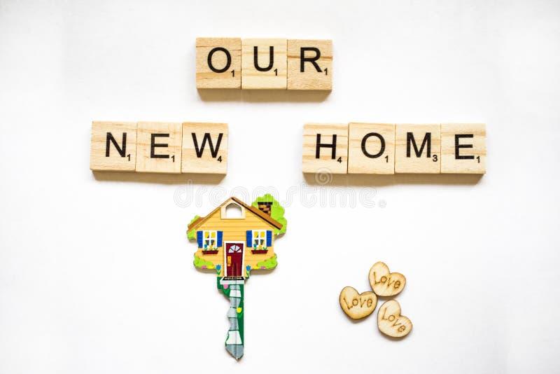 De sleutel is in de vorm van het huis op een witte achtergrond en houten blokken met het woord ons huis royalty-vrije stock afbeelding