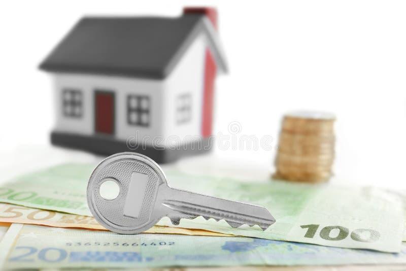 De sleutel met geld en stuk speelgoed huis, sluit omhoog royalty-vrije stock foto's