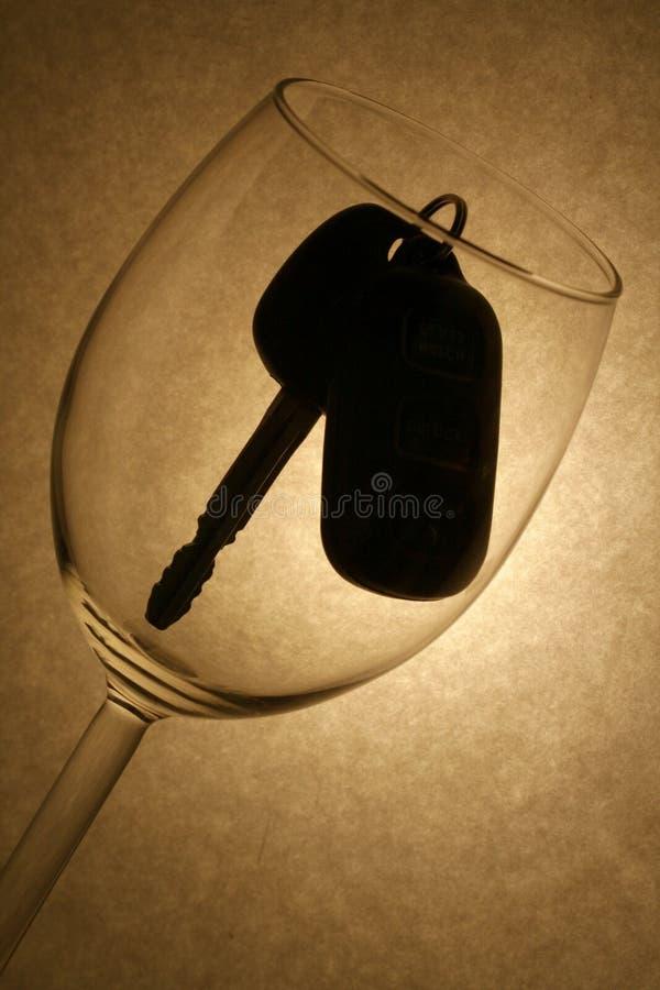 De sleutel van de auto in een wijnglas, gedronken bestuurder stock foto