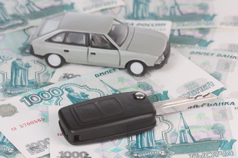 De sleutel van de auto op geld stock foto