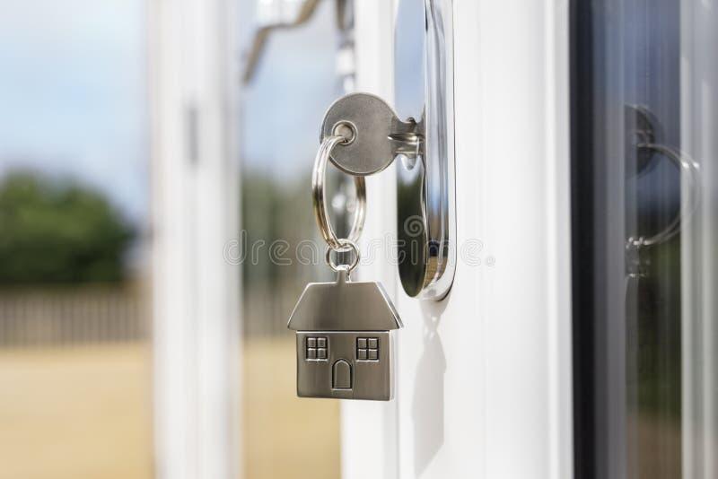 De sleutel van het huis op een huis vormde zilveren keyring in het slot van een deur stock fotografie