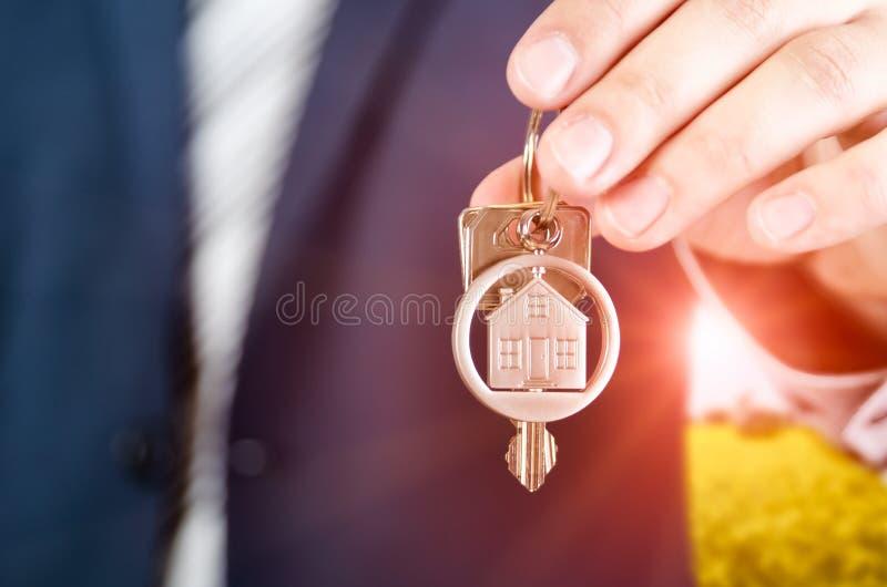 De sleutel van de makelaar in onroerend goedholding van nieuwe flat dichte omhooggaand stock foto's