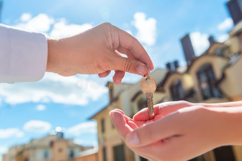 De sleutel van verkopersoverdrachten tot het huis in de handen van de koper stock foto