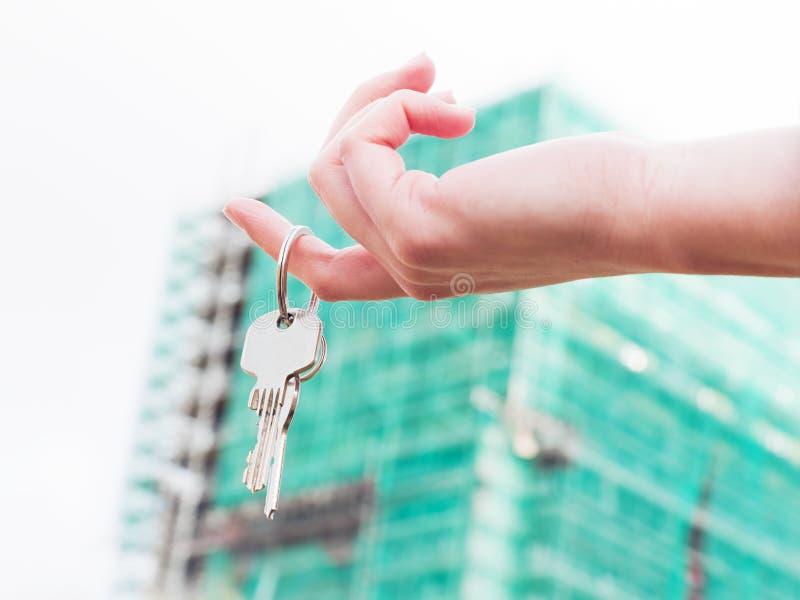De sleutels van een makelaar in onroerend goedholding tot een nieuw huis in haar handen. stock afbeeldingen