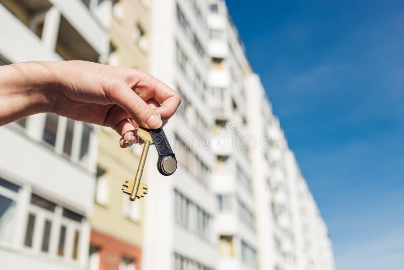 De sleutels van een makelaar in onroerend goedholding tot een nieuwe flat in haar handen De bouw van in aanbouw de Onroerende goe stock afbeeldingen