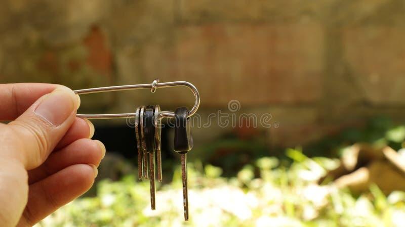 De Sleutels van de handholding in Veiligheidsspeld stock foto's