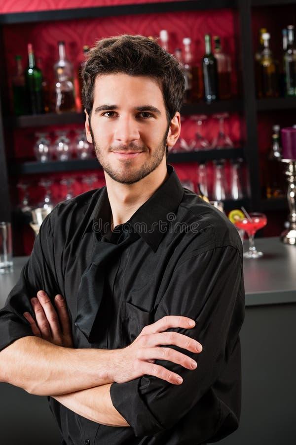 De slijtage van de barman zwarte status bij cocktailstaaf stock foto