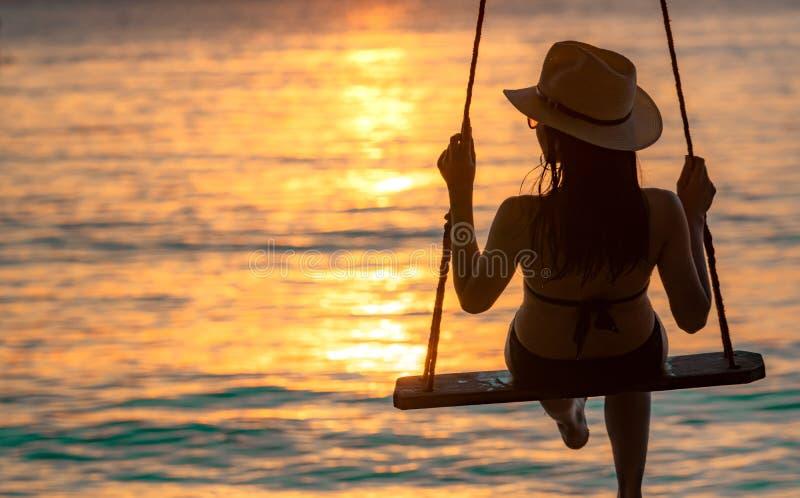 De de slijtagebikini van de silhouetvrouw en de strohoed slingeren de schommeling bij het strand op de zomervakantie bij zonsonde royalty-vrije stock fotografie