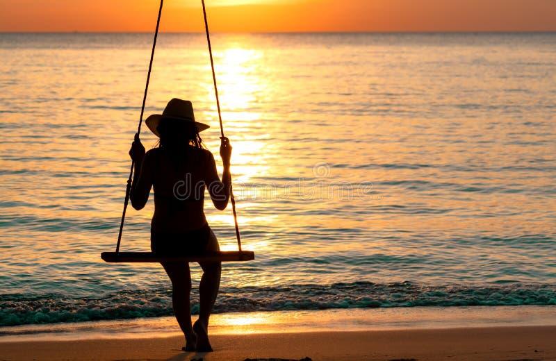 De de slijtagebikini van de silhouetvrouw en de strohoed slingeren de schommeling bij het strand op de zomervakantie bij zonsonde royalty-vrije stock afbeelding