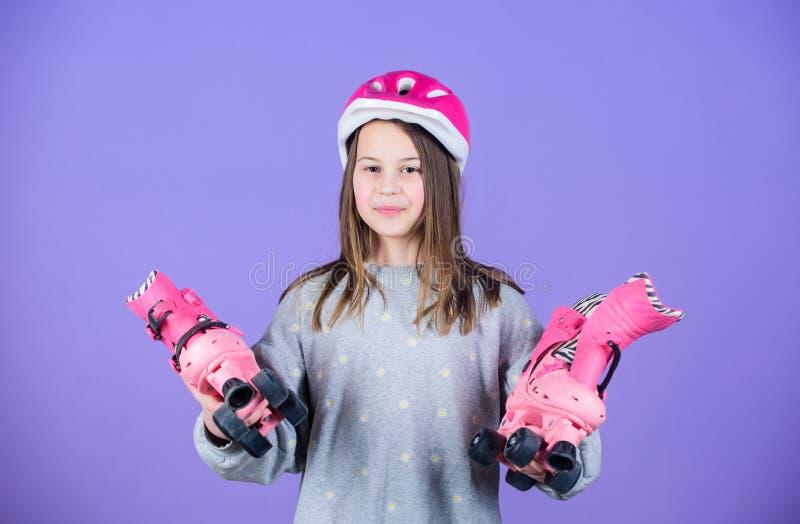 De slijtagehelm en rolschaatsen van de meisjes leuke tiener op violette achtergrond Actieve vrije tijd en levensstijl Rol schaats stock foto's