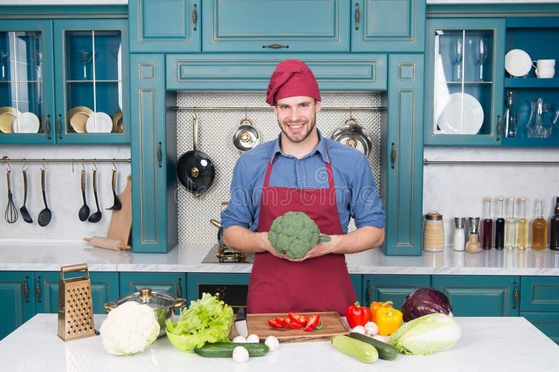 De slijtageschort van de mensenchef-kok het koken in keuken Het vegetarische recept van de mensenkok met verse groenten Vegetaris royalty-vrije stock afbeelding