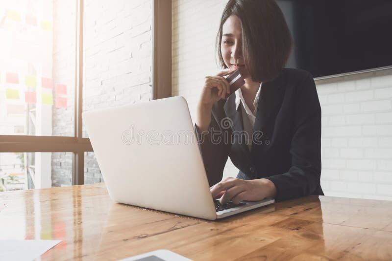 De slimme Aziatische creditcard van de vrouwenholding en het gebruiken van laptop computer stock afbeeldingen