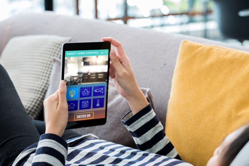 De slimme controle van de huisautomatisering concpet Vrouw die op bank liggen die het apparaat van de tabletcontrole in huis met  stock afbeeldingen