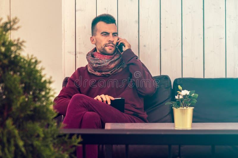 De slimme jonge mens werkt in openlucht aan tabletcomputer in koffie in stedelijke openbare ruimte stock afbeeldingen