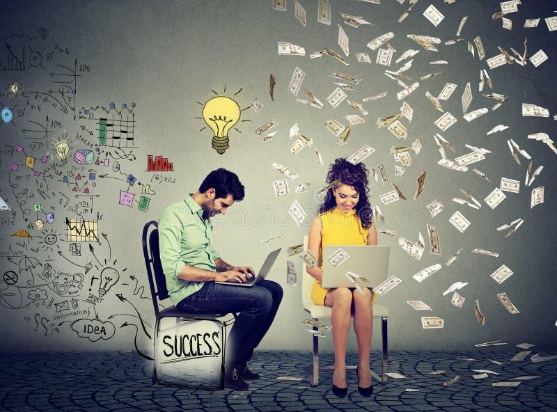 De slimme man die aan computer werken produceert ideeën naast een vrouw gebruikend laptop onder geldregen royalty-vrije stock foto