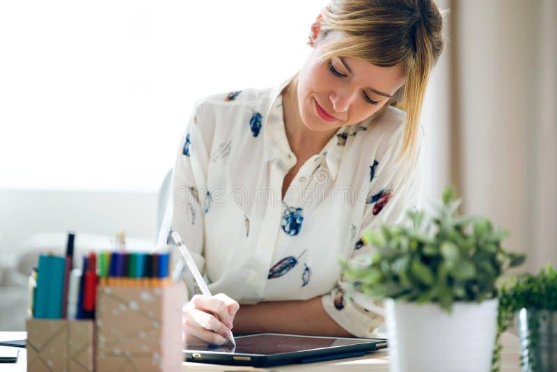 De slimme mooie jonge tekening van de ontwerpervrouw iets op haar digitale tablet op het kantoor royalty-vrije stock afbeeldingen