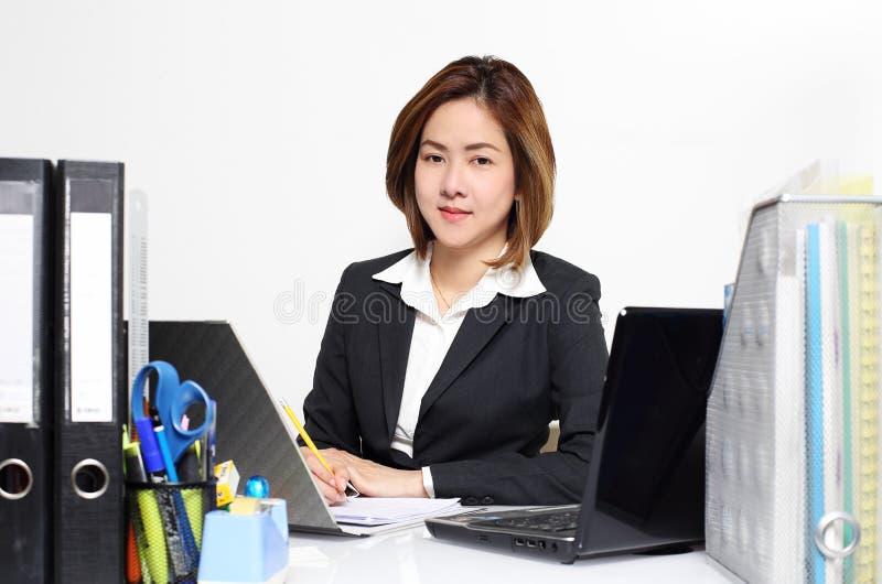 De slimme onderneemster Asian die in bureau aan de lijst werken royalty-vrije stock foto