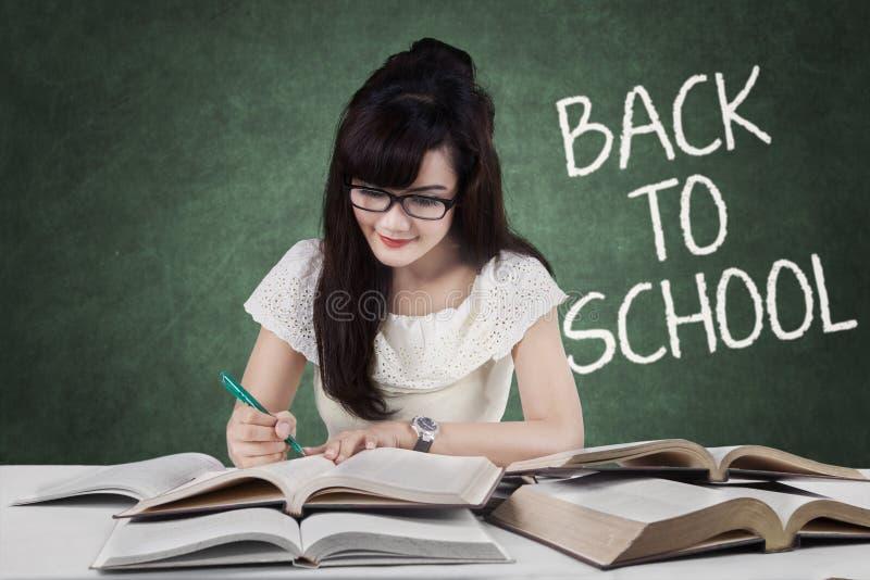De slimme student terug naar school schrijft op de boeken stock foto's