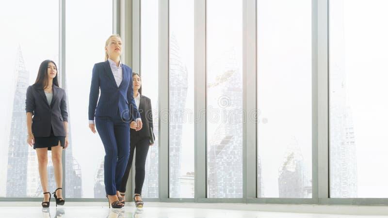 De slimme vrouwen bedrijfsmensen lopen op gangkantoor met façade glassing achtergrond en de moderne bouw groepswerk professionee royalty-vrije stock afbeeldingen