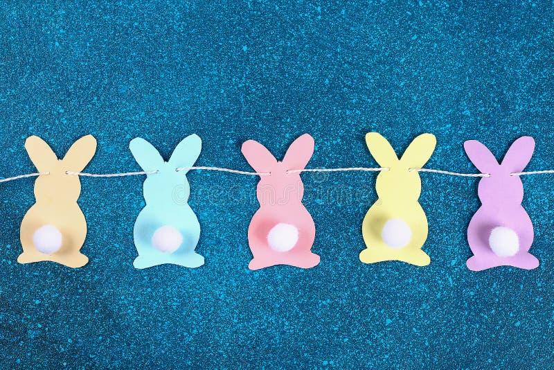 De slingerkonijntjes van Diypasen, vlaggenpasen gemaakt document blauwe achtergrond Giftidee, de decorlente, Pasen stock afbeeldingen