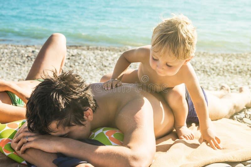 De slordige vermoeide papa wil niet met baby op strand spelen stock afbeeldingen
