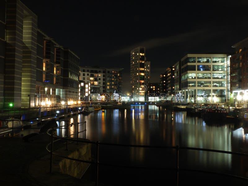 de de slotingang en meertrossen bij clarencedok in Leeds bij nacht met gebouwen van de ontwikkeling dachten in het water na en stock fotografie