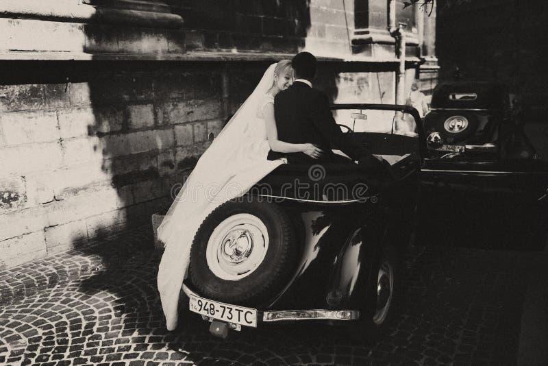 De sluier van de bruid hangt neer terwijl zij met bruidegom op een retro auto zit stock fotografie