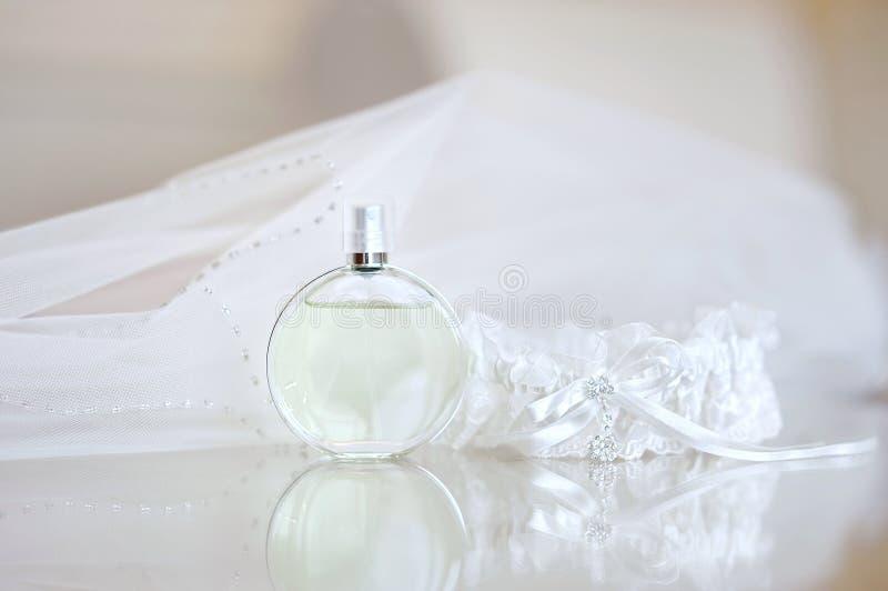 De sluier van het huwelijk, parfum en een kouseband stock foto