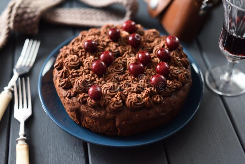 De smakelijke eigengemaakte chocoladecake met chocoladesuikerglazuur en de ruwe kersen dienden met rode wijn op donkere achtergro stock afbeeldingen