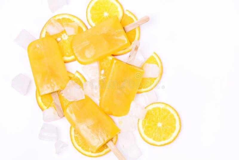 De smakelijke Eigengemaakte Ijslollys met Oranje Juice Ice Fruit Lollies op Hoogste het Weergevenvlakte van het Stokkenijsblokje  stock fotografie