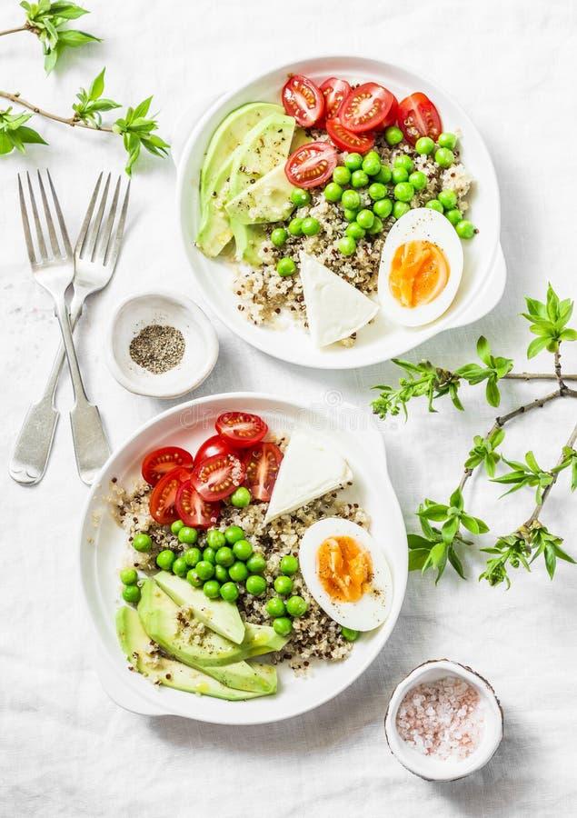 De smakelijke kom van de ontbijtkorrel De evenwichtige kom van Boedha met quinoa, ei, avocado, tomaat, groene erwt op lichte acht stock fotografie