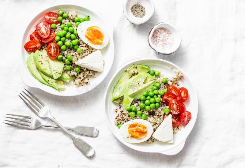 De smakelijke kom van de ontbijtkorrel De evenwichtige kom van Boedha met quinoa, ei, avocado, tomaat, groene erwt op lichte acht stock afbeeldingen