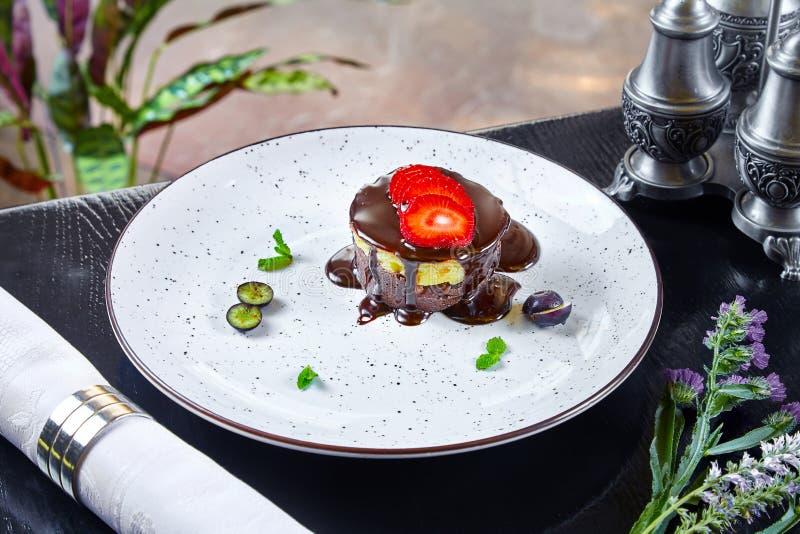 De smakelijke kwarkbraadpan goot met gesmolten chocolade en verfraaide met aardbeien en munt Restaurant het dienen stock foto's