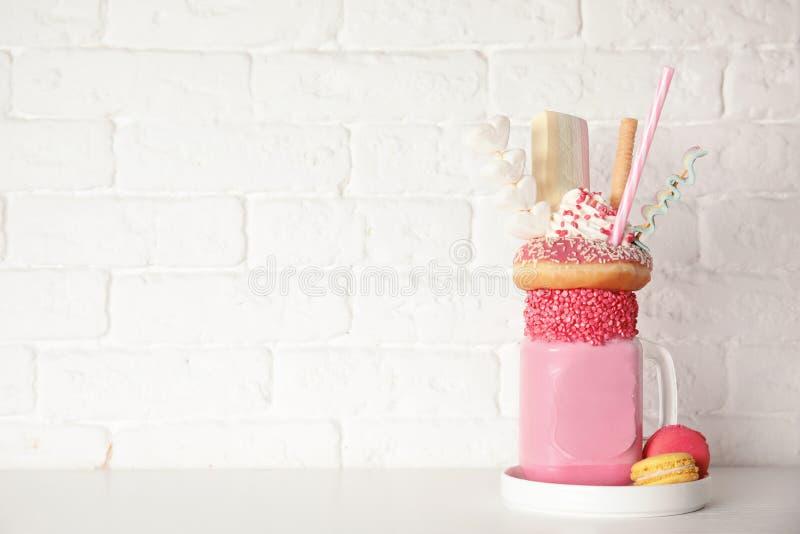 De smakelijke milkshake met snoepjes in metselaarkruik diende op lijst dichtbij bakstenen muur stock fotografie