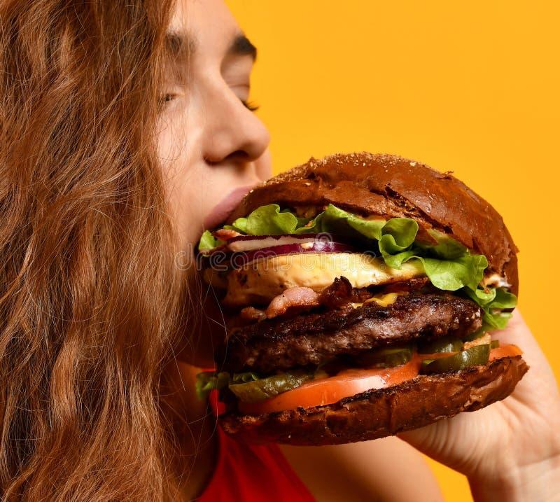 De smakelijke ongezonde hamburgersandwich in vrouw overhandigt hongerige mond die klaar te eten worden royalty-vrije stock fotografie